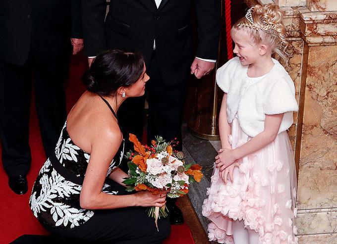 Chào đón vợ chồng Meghan khi đặt chân tới nhà hát là một bé gái 7 tuổi đeo vương miện. Không ngại đôi giày cao gót và chiếc váy dài vướng víu, Meghan ngồi thấp xuống để nhận hoa rồi ân cần trò chuyện với fan nhí.