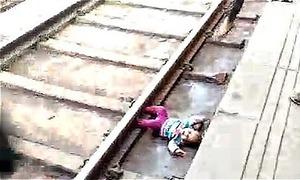 Bé 1 tuổi nằm dưới gầm tàu đang chạy