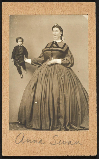 Giantess Anna Haining Bates, holding a small child for scale, 1888. Anna was 7 ft 11 inches tall