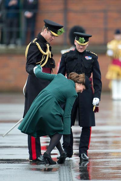 kate bám tay chồng để cố gắng rút giày cao gót ra khỏi rãnh cống. Ảnh: The Sun.