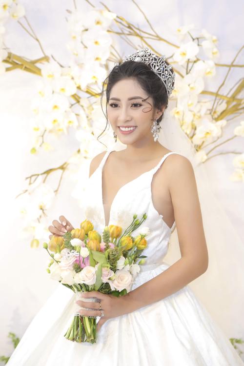 Hoa hậu chọn tóc búi cao giúp tổng thể bớt rườm rà, rối mắt khi diện váy cưới theo phong cách tối giản.