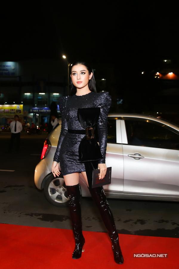 Huyền Mi chọn bốt cổ cao trên chất liệu da đen bóng để phối cùng mẫu váy đính nơ bắt mắt.