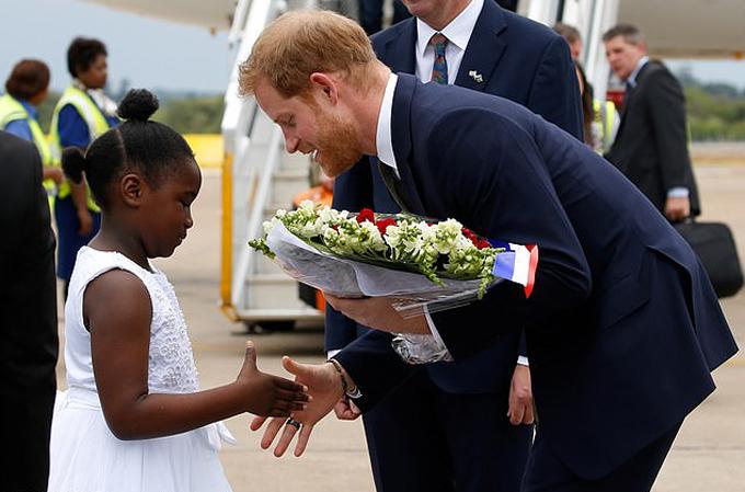 Hoàng tử Harry bắt tay cô bé Jane Chawanangwa, người đại diện trẻ em Zambia, ra tặng hoa và chào đón hoàng tử nước Anh ở sân bay Lusaka chiều 26/11. Ảnh: Reuters.