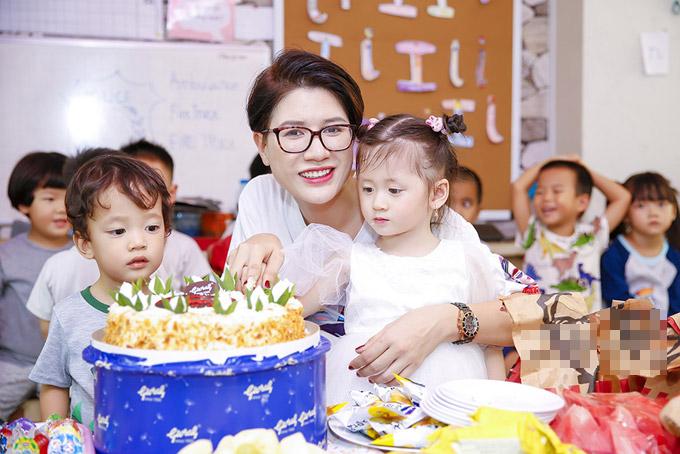 Trang Trần giúp con gái cắt bánh trong sinh nhật 3 tuổi của cô bé.