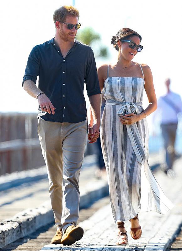 Hoàng tử Harry dắt tay vợ bầu Meghan cầu cảng đảo Fraser, Australia, chiều 22/10. Ảnh: Rex.