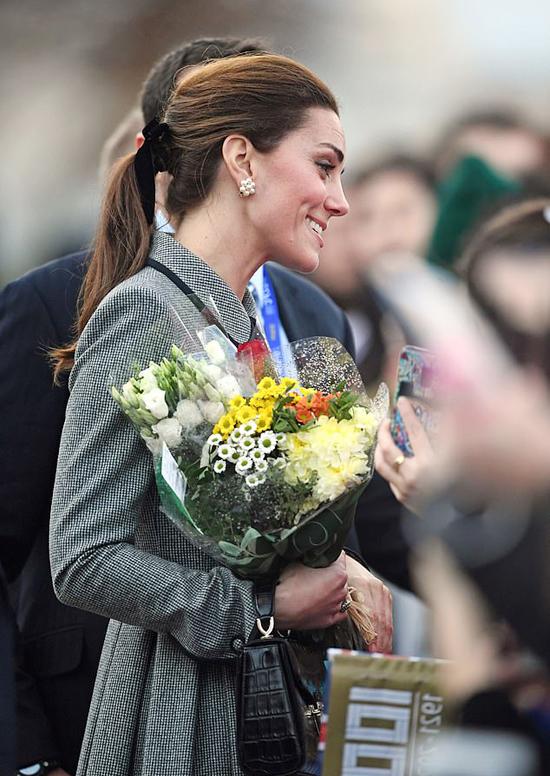 Kate nhận hoa từ người hâm mộ khi tới thăm thành phố Leicester hôm 28/11. Ảnh: AP.