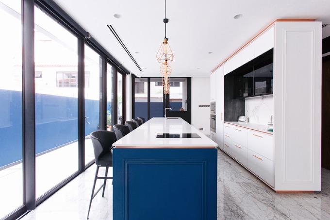 Tủ bếp màu trắng tạo sự hài hòa, êm dịu với những chi tiết mang sắc xanh dương và vàng hồng.