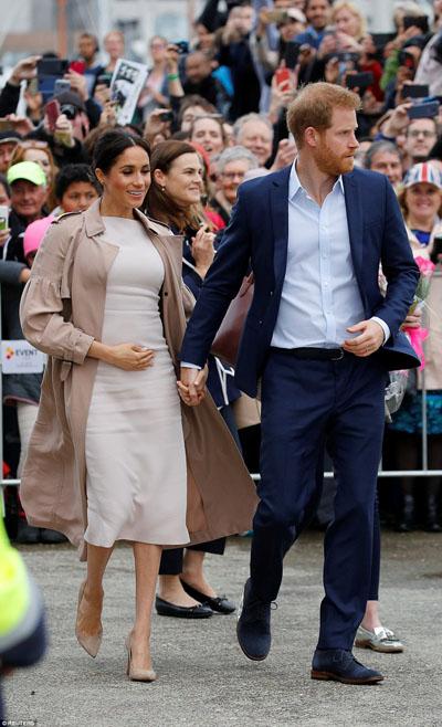 Meghan bế bụng bầu nắm chặt tay chồng khi cả hai đến thành phố Auckland, New Zealand, trong chuyến công tác hồi cuối tháng 10. Ảnh: Reuters.