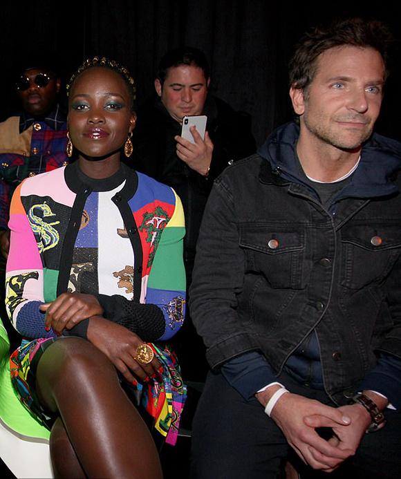 Bạn trai cô - tài tử Bradley Cooper ngồi xem show diễn bên cạnh nữ diễn viên 12 năm nô lệ Lupita Nyongo. Nam diễn viên mặc đồ mùa đông giản dị.