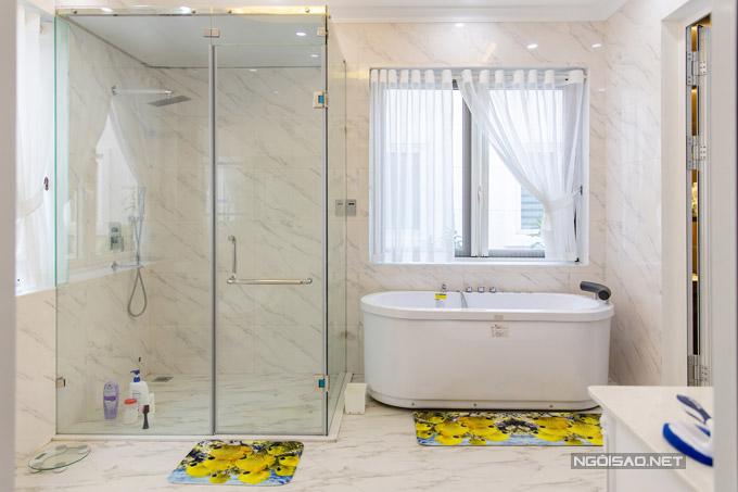 Phòng vệ sinh nối thông với phòng ngủ của Quang Hà được lát đá màu trắng có hoa văn. Anh đặt cả bồn tắm và làm vách kính.
