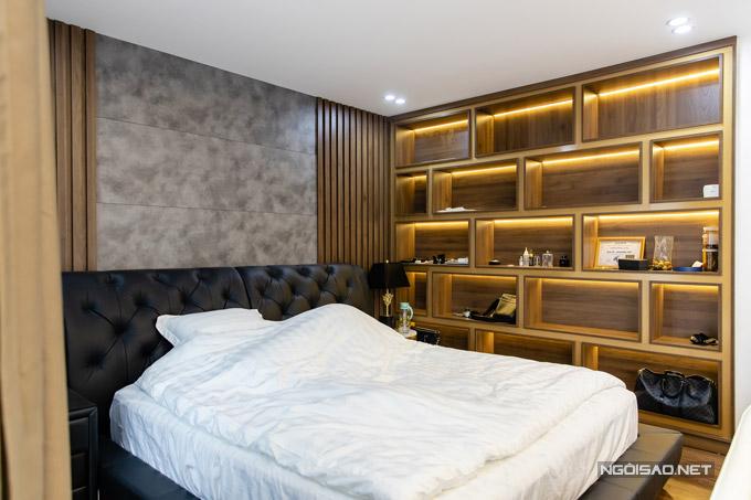 Giường ngủ của Quang Hà cũng được thiết kế tối giản nhưng vẫn đảm bảo nét sang trọng. Ở một góc tường anh cho đóng giá gỗ lớn để làm những ngăn trưng bày nước hoa, mỹ phẩm và nhiều đồ dùng cá nhân khác.