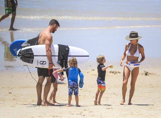 Các con của cặp đôi thích thú vui đùa trên bãi biển.