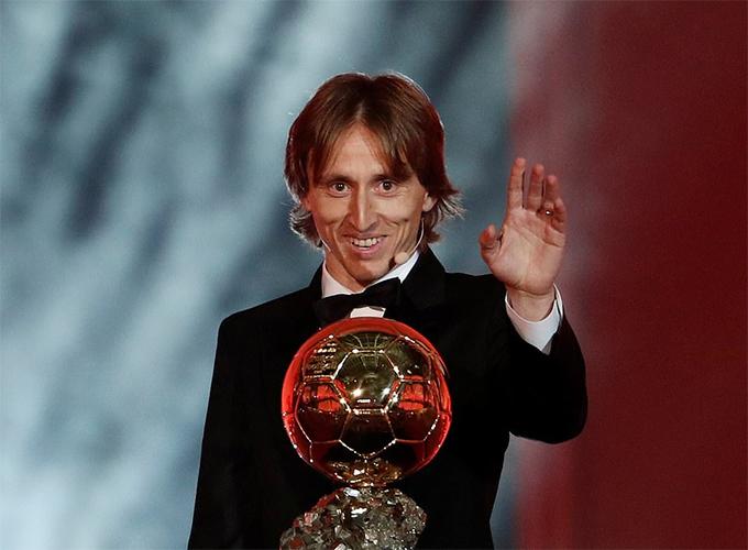 Modric cười tươi khi lên sân khấu nhận Quả bóng vàng. Ảnh: Reuters.
