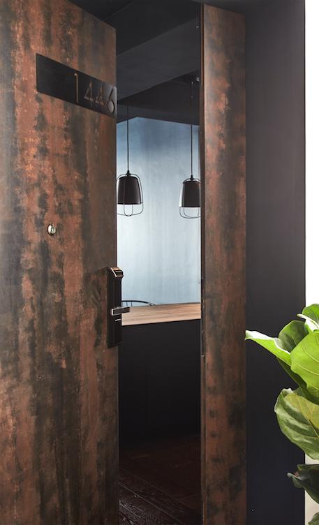 Cánh cửa chính có màu sắc giống như một tấm kim loại nhiều tuổi, tương phản với những mảng gỗ khác trong phòng.