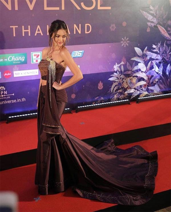 Hoa hậu cho biết, chiếc váy đuôi cá chất liệu lụa Thái Lan này được chính công chúa Sirivannavari thiết kế. Công chúa Thái Lan vốn là người mộ điệu thời trang và đam mê công việc thiết kế. Sirivannavari từng mang bộ sưu tập đầu tiên của cô tới trình diễn tại Tuần lễ thời trang Paris.