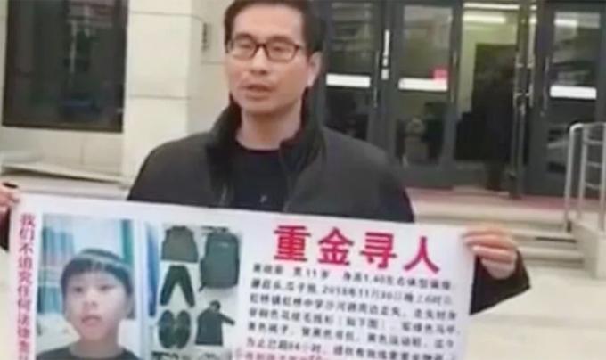 Chồng của Chen cầm poster về con trai mất tích hôm 3/12 ở thành phố Nhạc Thanh, Ôn Châu, Trung Quốc. Ảnh: Weibo.