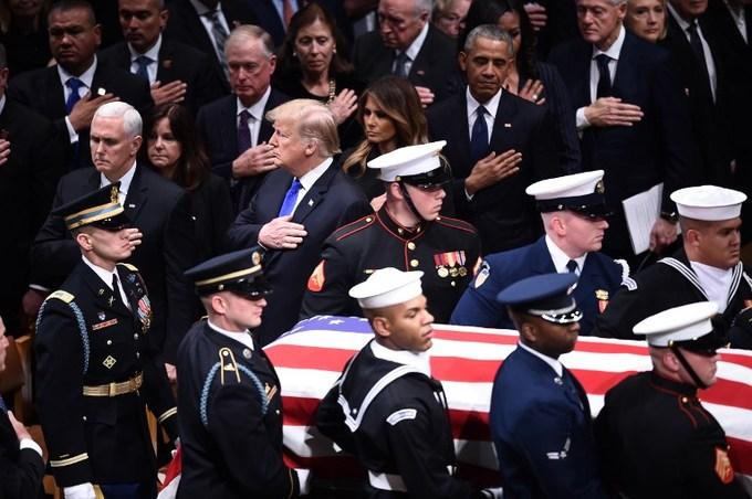 Các cặp vợ chồng tổng thống đứng lên, đặt tay lên ngực trái để thể hiện sự tôn kính khi linh cữu cố tổng thống Bush được đưa vào nhà thờ. Ảnh: AFP.