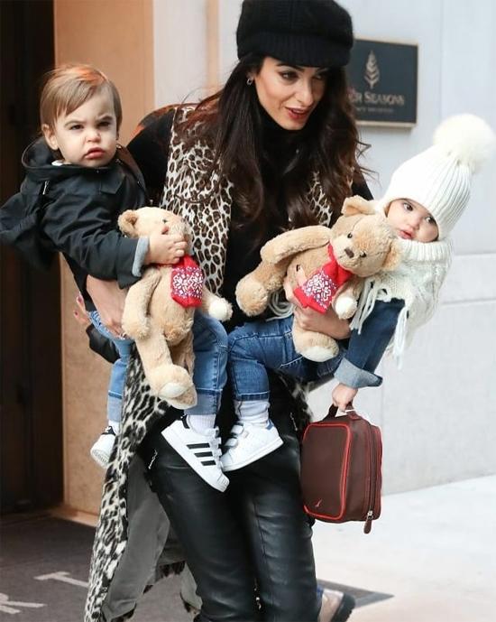 Amal Clooney hai tay bế hai con sinh đôi rời khách sạn hôm thứ 5.