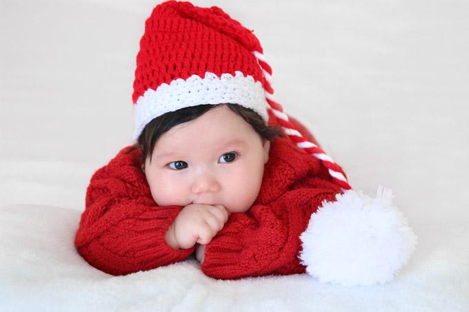 Nàng công chúađược bố mẹ cho mặc trang phục mang màu sắc Giáng sinh vô cùng đáng yêu. Cô bé không quan tâm đến ống kính mà mải mê gặm tay.
