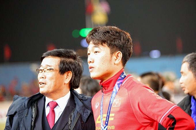 Xuân Trường đứng nói chuyện với bố trên sân trước khi ra khán đài tìm mẹ. Ảnh: Đương Phạm.