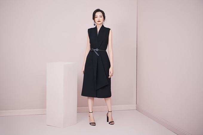 Vẻ sang trọng của đầm cổ vest đen không chỉ toát ra từ loại chất liệu cao cấp, mà còn từ thiết kế tối giản nhưng không hề nhạt nhoà với điểm nhấn thắt lưng mảnh giúp định hình form dáng.