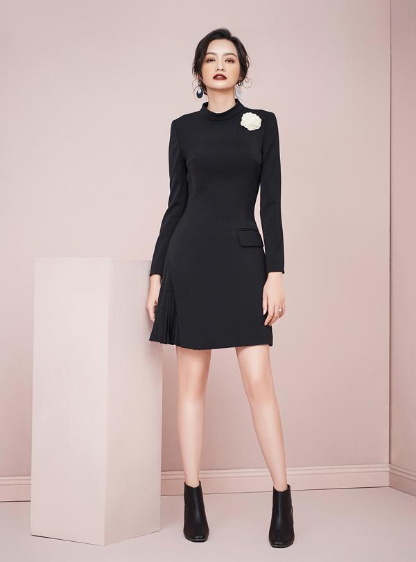 Trên gam màu đen tối giản, thiết kế đầm trơn với phần trên ôm sát, phần chân váy xoè nữ tính được tạo điểm nhấn bằng hoa chi tiết hoa trà lụa đính ngực, tối giản nhưng sang trọng, tinh tế.