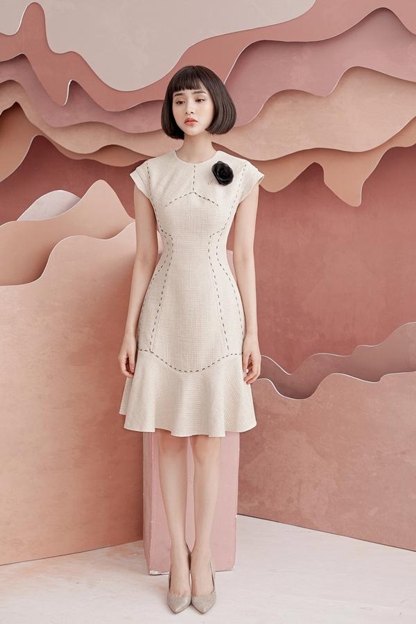 Nhà thiết kếkhai thác kiểu váy phom dáng đơn giản, phù hợp nhiều hoàn cảnh khác nhau như công sở, đi tiệc...  Những đường chỉ viền quanh eo và chân váy, kết hợp hoa cài giúp Hiền Hồ thêmngọt ngào.