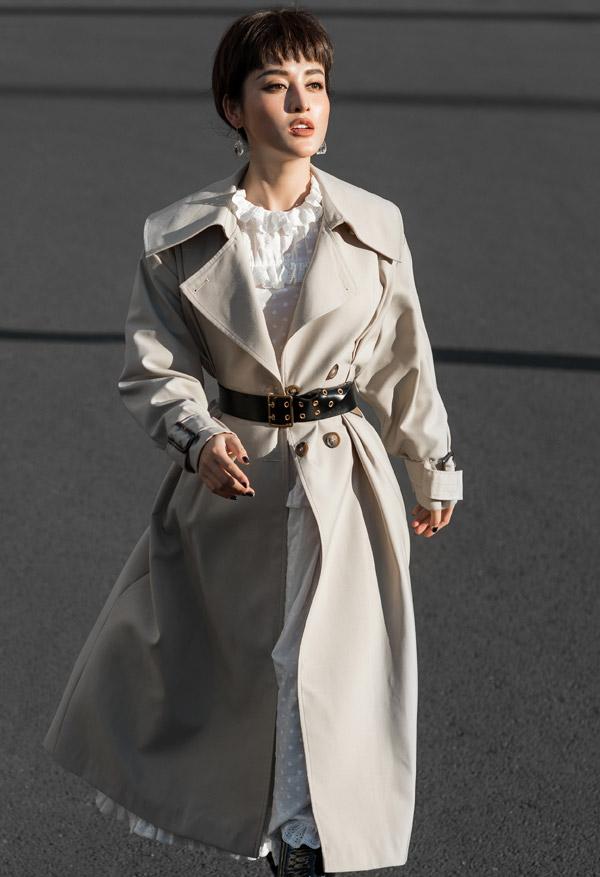 Váy trắng cổ điển phối hợp cùng áo khoác oversizetạo cho Á hậu vẻ ấn tượng.