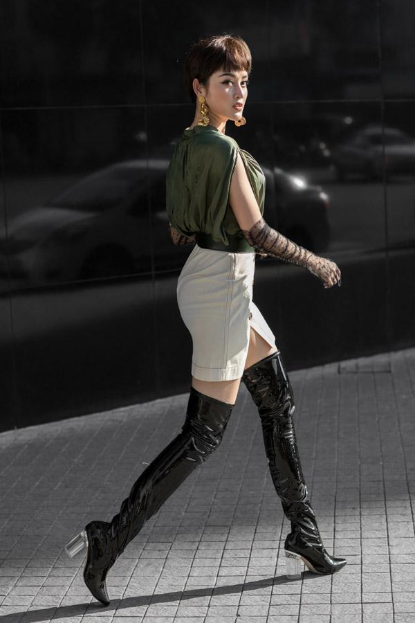 Boots đen da bóng cao quá đầu gối với chi tiết gót trong suốt là món phụ kiện cô yêu thích.