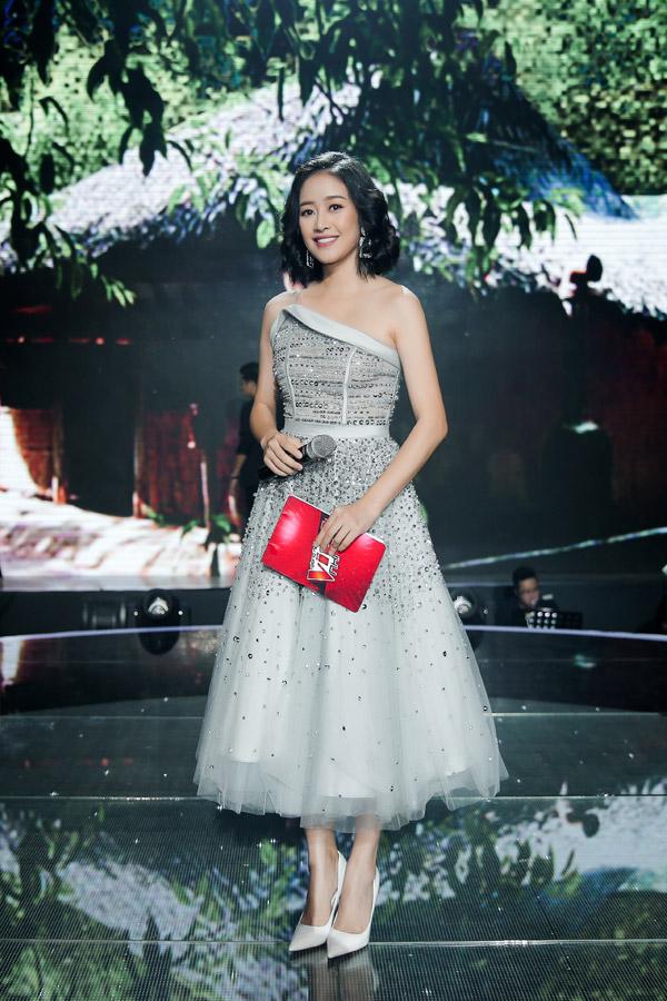 Mẫu váy xòe cổ điển do NTK Tăng Thành Công thực hiện với điểm nhấn lệch vai lại giúp Phí Linh thêm phần điệu đà. Trang phụcbắt mắt hơn nhờ những hạt pha lê đính cầu kỳ dọc thân váy.