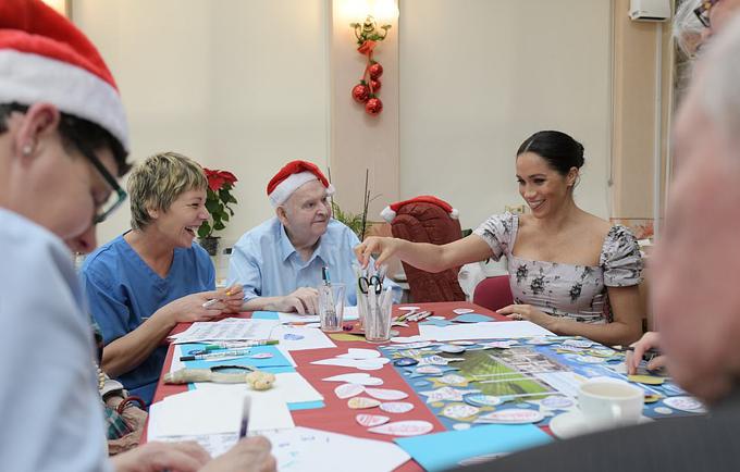 Sau cuộc họp ngắn, Meghan gặp bốn cư dân của viện dưỡng lão trong phòng ăn và cùng làm đồ trang trí Noel.