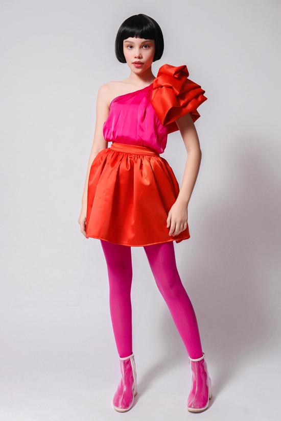 Nhà thiết kế Thanh Huỳnh kết hợp gam màu tương phản nóng - lạnh tạo ấn tượng thị giác cho trang phục. Phần chân váy xếp lớp và nơ to bản màu xanh nhấn nhá cho tổng thể.