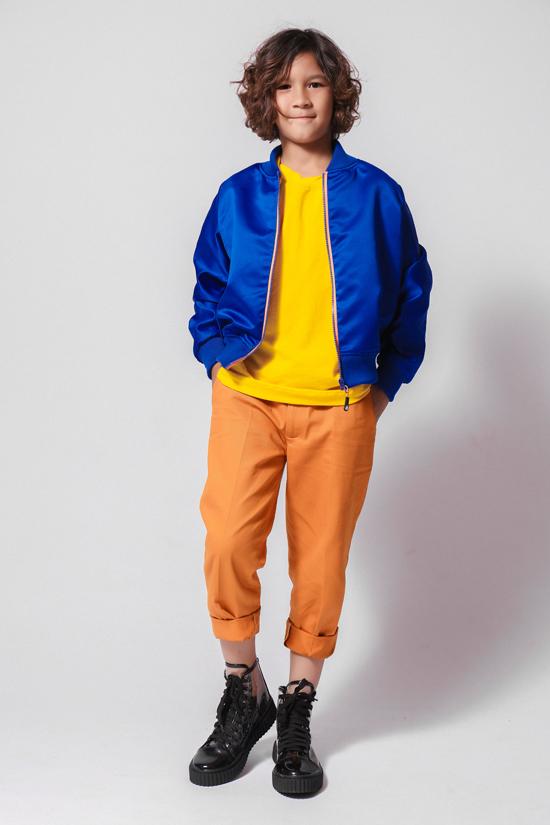 Kelvin thừa hưởng tình yêu thời trang từ mẹ là nhà thiết kế Thanh Huỳnh và bố là danh thủ bóng đá Kesley. Cậu bé có mái tóc lãng tử và gương mặt lai điển trai yêu thích bomber gam xanh. Trang phục đa sắc có thể ứng dụng cho các bé đi học, đi chơi.