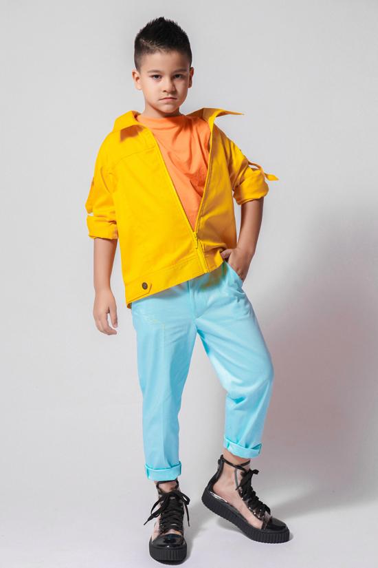 Kaylan - em trai Kelvin tuy nhỏ tuổi nhưng tự tin tạo dáng trước ống kính. Áo khoác ngoài tông vàng rực rỡ giúp Kaylan nổi bật giữa đám đông. Bên cạnh công việc mẫu nhí, hai anh em còn sở hữu nhiều tài lẻ như đánh trống, ca hát.
