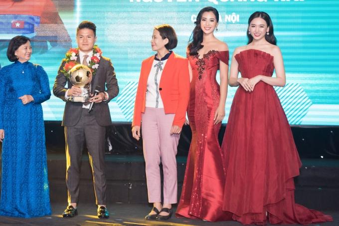 Quang Hải lên sân khấu nhận cúp Quả bóng vàng 2018. Với chiều cao khiêm tốn, anh có phần nhỏ bé khi đứng gần hai người đẹp Tiểu Vy và Hari Won.