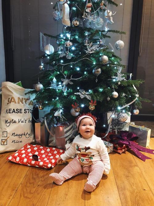 Bé Myla 6 tháng tuổi trôngmũm mỉm, có đôi má phụng phịu, làn da trắng hồng, mái tóc đen dày và đôi mắt tròn xoe.