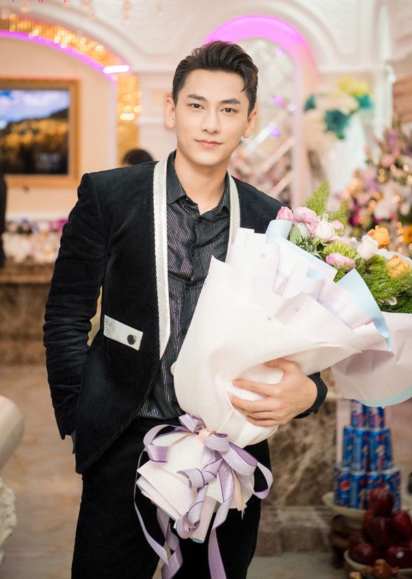 Isaac diện vest đen bảnh bao và biểu diễn tại sự kiện.