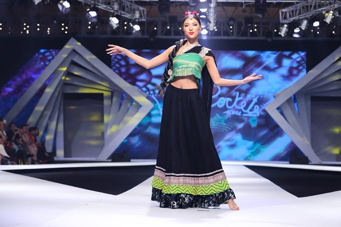 Khả Trang đi chân trần, nổi bật trong sari truyền thống của Ấn Độ. Siêu mẫu còn thể hiện khéo léo động tác múa của người Ấn khiến khán giả thích thú.