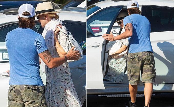Nam diễn viên nhạc đồng quê ân cần đỡ vợ vào xe.
