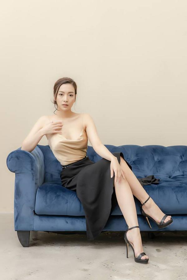 Huyền Quỳnh gợi cảm hơn với set áohai dây màu nude mix chân váy đen.