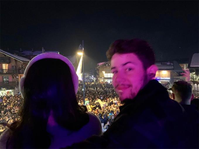 Cặp sao đứng trên ban công, ngắm quảng trường đông đúc và chờ đợi khoảnh khắc năm mới đến.
