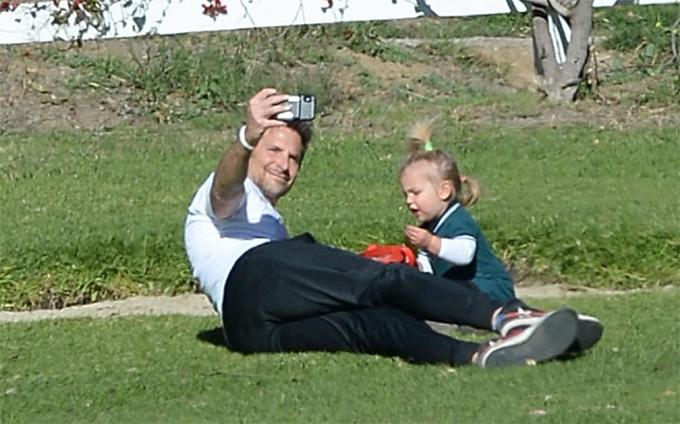 Bradley Cooper oằn người tạo dáng để tìm góc chụp ảnh selfie hai bố con.