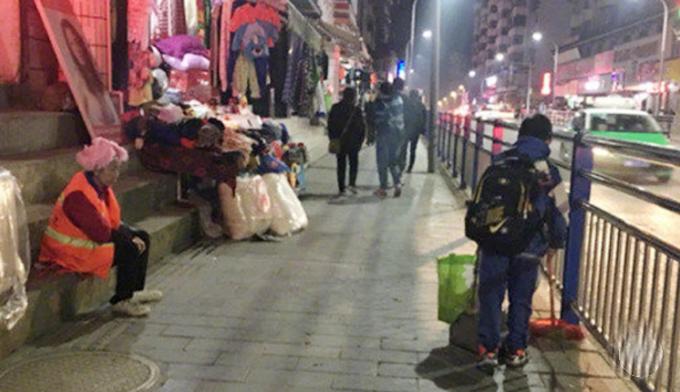 Guotao quét dọn vệ sinh trong khi chị Wu Azhen, mẹ của cậu bé, tạm ngồi nghỉ sau ngày dài mệt nhọc. Ảnh: Weibo.