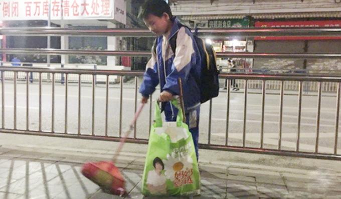 Guotao cầm chổi quét dọn trên đường phố Khải Lý, Quý Châu, Trung Quốc. Ảnh: Weibo.