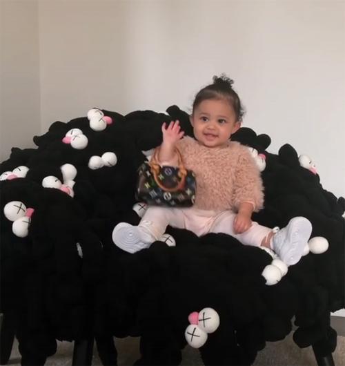 Con gái Kylie xách túi Louis Vuitton tạo dáng trên ghế.
