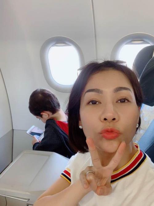 Ca sĩ Thu Minh nhí nhảnh tạo dáng selfie trong khi con trai mải xem điện thoại trên máy bay.