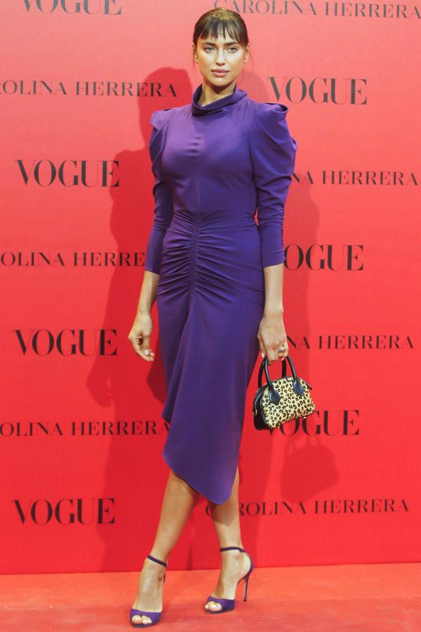 Irina ShaykBộ đầm màu tím kín cổng cao tường không chỉ đơn điệu, lỗi mốt mà còn khiến siêu mẫu Nga trông tròn trịa hơn.