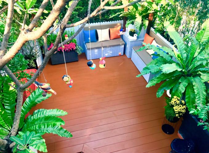 Góc vườn sau khi cải tại được lát gỗ (loại dùng ngoài trời) và lắp mái che bằng chất liệu có khả năng hứng sáng.Chị Hiền là người trực tiếp thiết kế, giám sát thi công và thực hiện trang trí cho khu vườn. Khu vực sinh hoạt chung này của gia đình có diện tích khoảng 30 m2, tích hợp để trồng các loại hoa, đặc biệt là hoa hồng.Khi cải tạo vườn, việc đầu tiên chị Hiền chú trọng là làm lại hệ thống thoát nước. Vì hệ thống cũ có một số rễ cây ăn vào. Gia cố, chống thấm lại mặt sàn, tạo độ dốc cho nước thoát về một nơi dễ dàng; nâng sàn giả vừa để tăng thẩm mỹ, vừa cân lại mặt sàn, tránh nước ứđọng. Tại khu vực có mái che, chị bố trí 2 băng ghế ngồi đồng thời là hộc chứa dụng cụ làm vườn.
