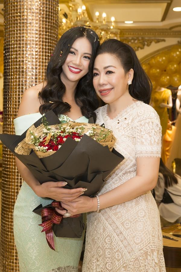Phương Khánh diện váy trễ vai màu xanh ngọc bích, vui vẻ tặng hoa và chụp ảnh cùng nhà thế kế Linh San.