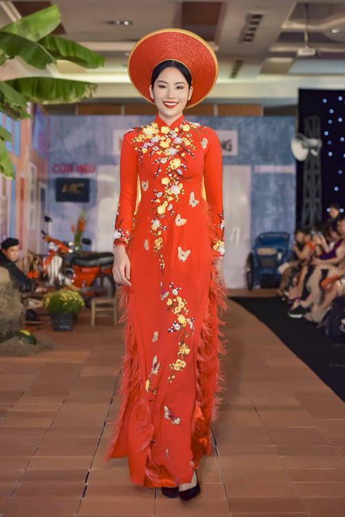 Người mẫu Nam Anh diện áo dài đỏ với điểm nhấn là cành hoa mai và những cánh bướm được trải dài dọc thân,